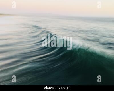 A speed blur of a wave breaking. Manhattan Beach, California USA. - Stock Image