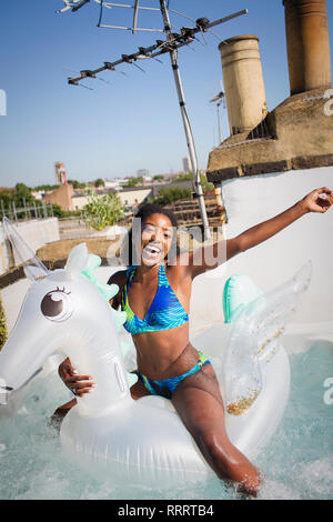 Portrait playful, carefree young woman in bikini on inflatable pegasus in sunny rooftop hot tub - Stock Image