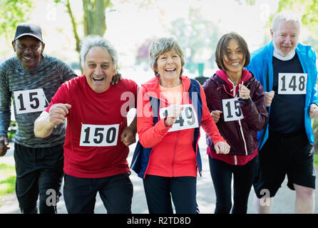 Portrait enthusiastic active senior friends running sports race - Stock Image
