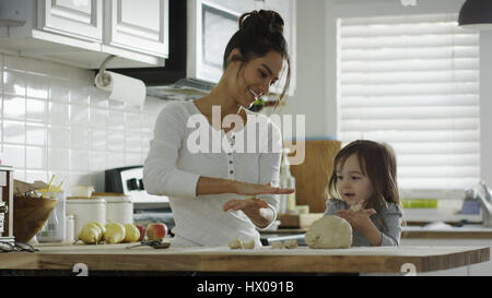 Smiling mother teaching daughter to bake and roll dough in kitchen - Stock Image
