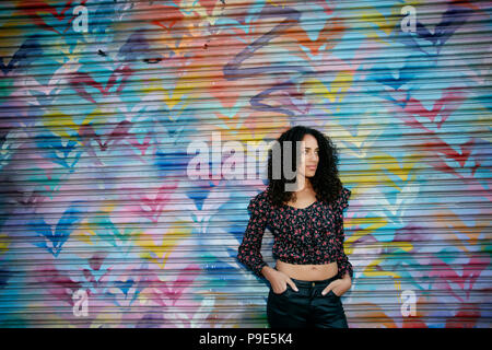 Young woman with black curly hair standing in front of shutter covered in colourful graffiti. - Stock Image