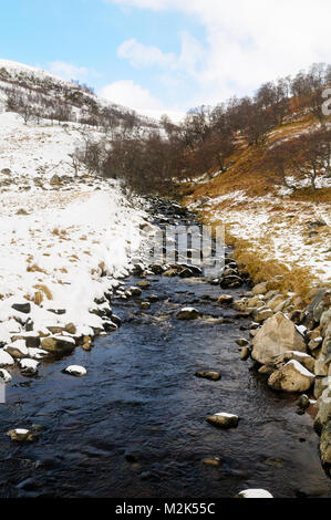 The rocky stream Allt Calder shortly before it joind the River Findhorn, in the snow-covered Monadhliath Mountains - Stock Image