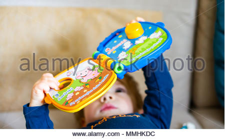 Baby boy playing with a Fisher Price electric book on a bench - Stock Image
