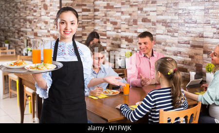 Girl is ready to serve salad and juice to young visitors of family cafe. - Stock Image