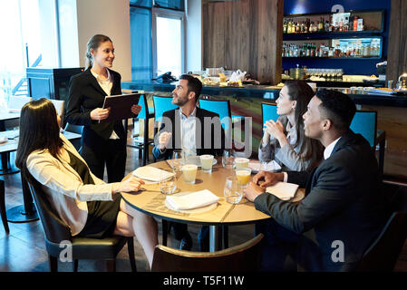 Waitress taking orders from business people in bar - Stock Image