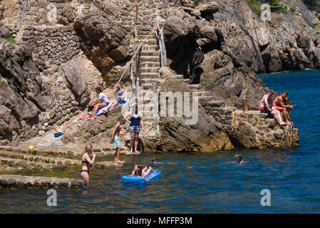 People enjoy a warm sunny day by the water`s edge in Cala Deia, Mallorca, Spain. - Stock Image