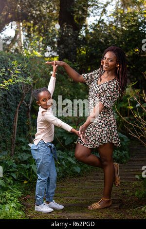 A mother and daughter playing on a garden path - Stock Image