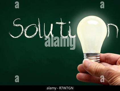 Man holding illuminated bulb with bare hands against chalkboard with the word Solution. Concept of bright idea, innovation, imagination, inspiration,  - Stock Image