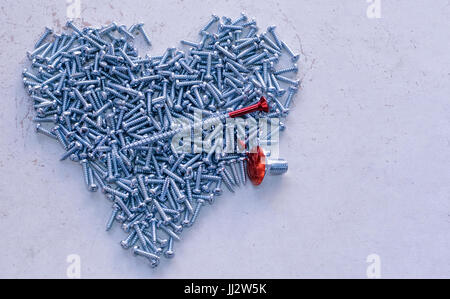 Massy screws heart with red screws - Stock Image