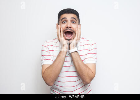 Portrait of surprised handsome bearded young man in striped t-shirt standing with hands on face and looking at camera with amazed face. indoor studio - Stock Image