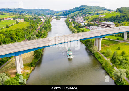 A leisure boat under high bridge where A13 motorway meets 8 highway over Moselle river. Aerial view of Schengen town center. Tripoint of borders of Lu - Stock Image