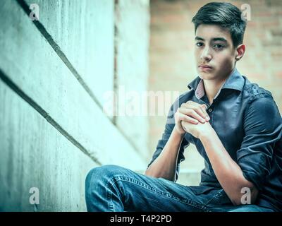 Boy, teenager, 14 years, sitting on stairs, direct view, look, portrait, Germany - Stock Image