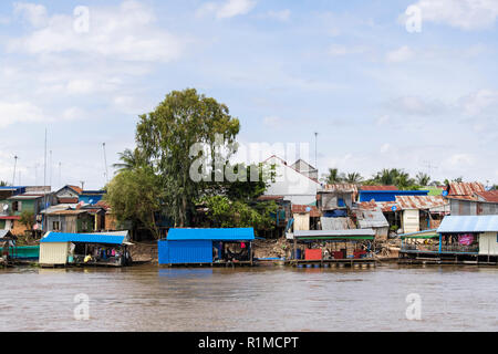 Typical tin houses on stilts in slum shanty town village along Mekong River. Cambodia, southeast Asia - Stock Image