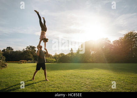 Strong young couple doing pair yoga outdoor in park. Man lifting and balancing woman in park. Acroyoga workout on - Stock Image