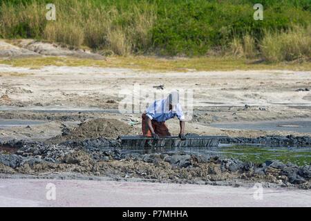 Salt Pans, Pan, Salt Miner, Mud Levelling, Ugandan Man, Crater Lake at Queen Elizabeth National Park, Uganda - Stock Image