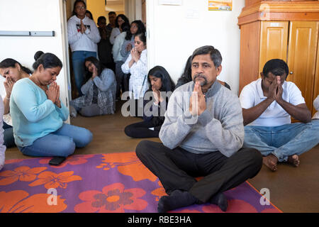 After services & prior to feeding the monks, worshippers sit and pray & meditate. At a Buddhist temple in Queens Village, New York City. - Stock Image