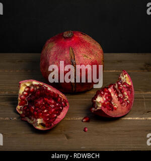 Two pomegranate fruits, one whole and one open, against wooden table, top view- healthy food concept - Stock Image