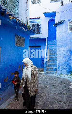 Chefchaouen, Morocco : A Moroccan woman and a child walk in the blue-washed medina old town. - Stock Image