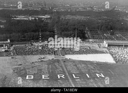 View of the facilities of the Berlin-Tempelhof Airport with the inscription Berlin. In front of the production hall is a gyrocopter. - Stock Image