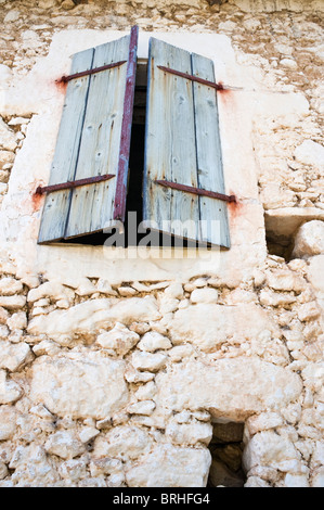Dilapidated old stone house with faded blue shutters Crete Greece - Stock Image