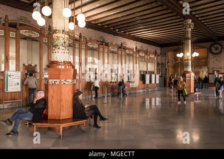 Travellers at Estacion del Norte (North Station), a Modernista building with ornate interior, South Ciutat Vella district, Valencia, Spain. - Stock Image