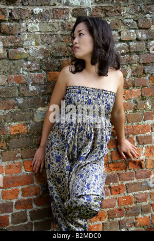 Chinese Girl Standing in Front of a Brick Wall - Stock Image