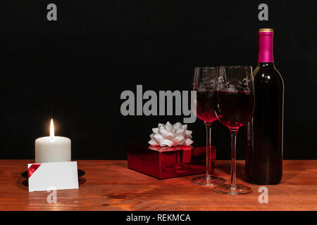Beautiful etched wine glasses and bottle of red wine, white candle, wrapped present with bow on wooden table with name tag on dark background. Valenti - Stock Image