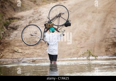 man carries bike through river in Saadani Tanzania Africa - Stock Image