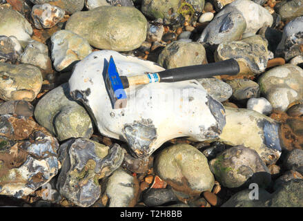 A geological hammer on a large flint on the beach at East Runton, Norfolk, England, United Kingdom, Europe. - Stock Image