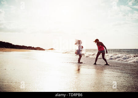 Happy mother and daughter having fun on tropical beach at sunset - Family playing next see during summer vacation - Stock Image
