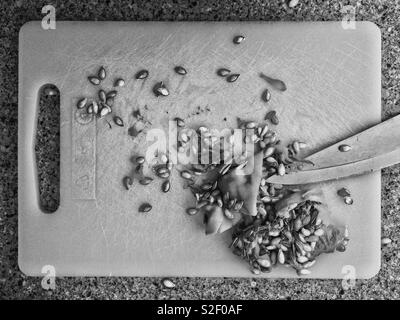 Black and white photo of kitchen worktop with chopping board and pulp and seeds of butternut squash with knife. - Stock Image