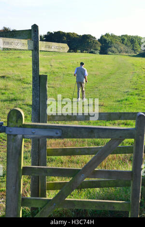 Walker ,having passed through the kissing gate is walking across field at Dell Quay,Chichester Harbour, West Sussex - Stock Image