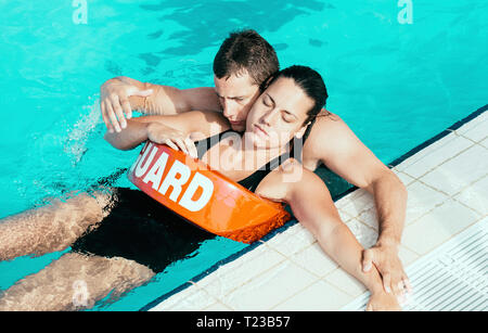 Lifeguard helping young woman after swimming pool accident. - Stock Image