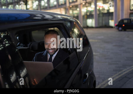 Smiling businessman using laptop in crowdsourced taxi at night - Stock Image
