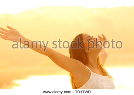 Happy woman stretching arms breathing deep fresh air at sunset on the beach - Stock Image
