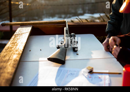 A 22 caliber rifle sits on a table while a young person learns about gun safety in Pennsylvania, United States. - Stock Image