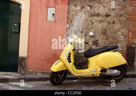 A yellow scooter parked outside of a small Italian door in Sicily, Italy. - Stock Image