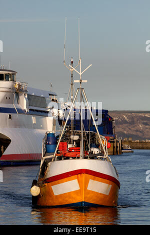 A small colourful fishing trawler comes back into Weymouth port after a nights fishing in Dorset - Stock Image