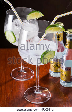 Gin and tonic, modern style - globe glass, lots of ice, slices of cucumber and lime and one  straw - Stock Image