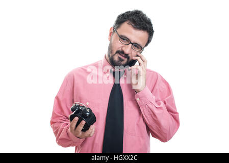 Smiling man with alarm clock talking at his smart phone - Stock Image