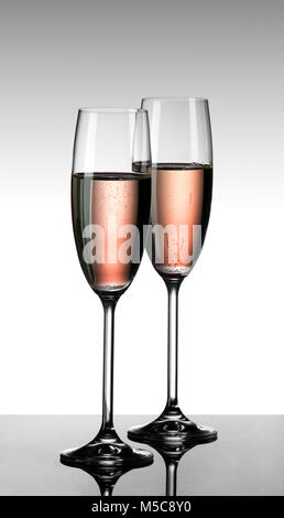 Pink champagne in two glasses on glass table with grey-white gradient background - Stock Image