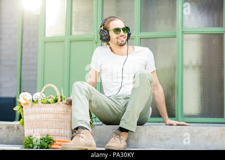 Portrait of a happy man listening to the music with headphones sitting outdoors on the green background - Stock Image