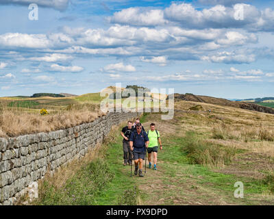 11 August 2018: Hadrian's Wall, Northumberland - Group of male hikers with walking poles walking on the Hadrians' Wall path at Walltown Crags on a war - Stock Image