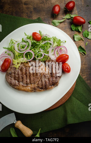 Grilled meat steak with arugula, sweet onion rings and cherry tomatoes. Cafe menu on a wooden background in warm colors with copy space. - Stock Image