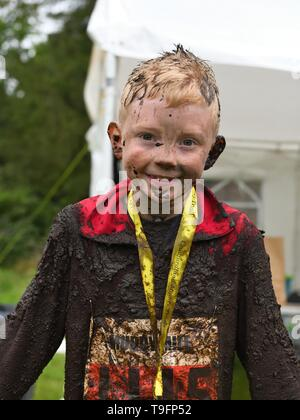 18th, May, 2019. Craufurdland Estate, Fenwick, Ayrshire, Scotland, UK. Participants have fun taking part in the 5k, 10k and the children's 1 mile 'Muddy Trial fun run through woods and ditches full of water and mud in the Craufurdland Estate. - Stock Image