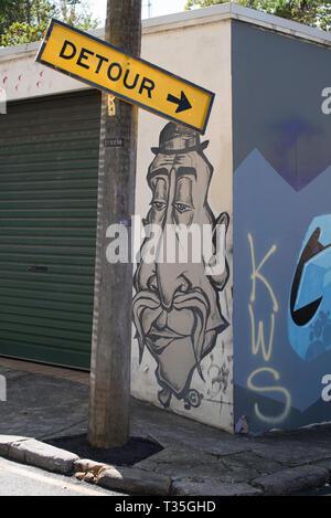 Street art painted beside a roller door of a garage in a back street in Surry Hills, Sydney Australia - Stock Image