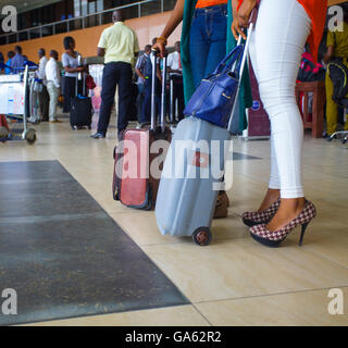 Young ladies dressed in trendy jeans  and high heels waiting for their flight at the Murtala Muhammed Airport, Lagos. - Stock Image