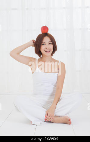 Young woman sitting on the floor with an apple on head, - Stock Image
