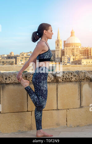 woman wearing sportswear doing a quad stretch outside in the sunshine with Valletta, Malta in the distance. - Stock Image