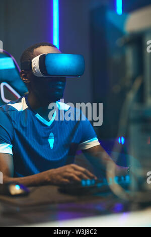 Serious concentrated black gamer in VR headset sitting at table and using computer while playing football video game - Stock Image